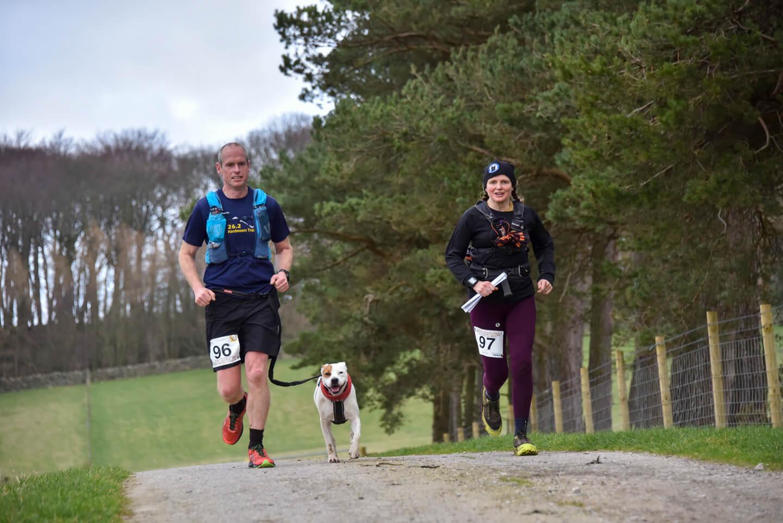 Man with dog and woman all running through parkland during an ultramarathon race.