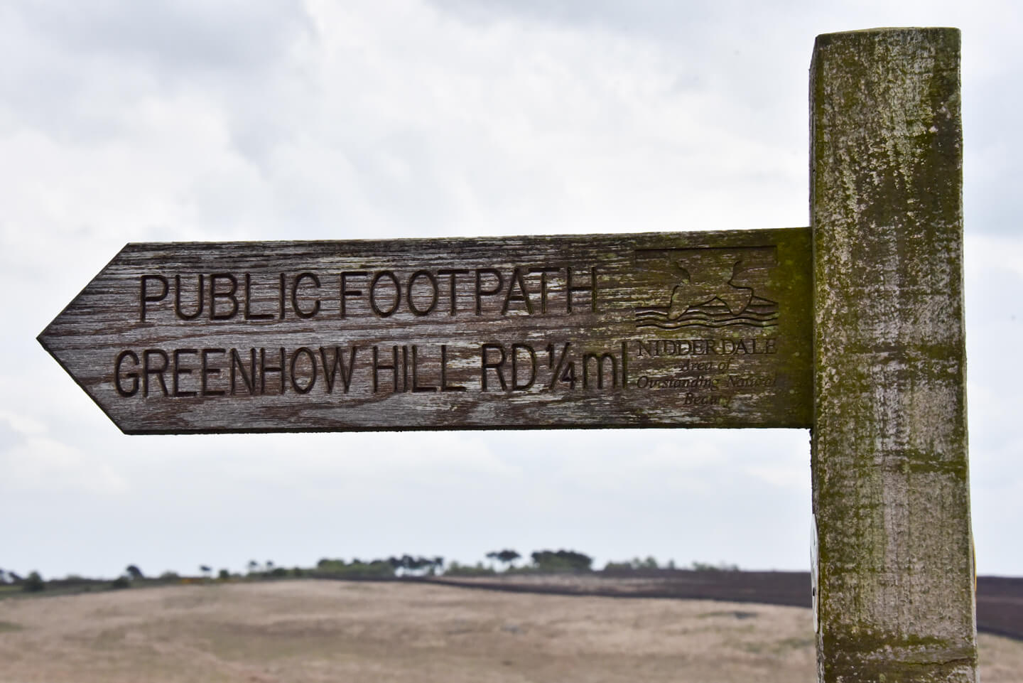 A wooden moorland signpost which points to the left and reads 'Public Footpath Greenhow Hill Road 1/4ml' It also has a carved stamp which reads Nidderdale area of outstanding beaty.