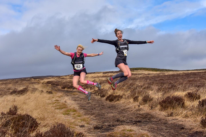 Two girls jumping for joy over moorland during an ultramarathon.