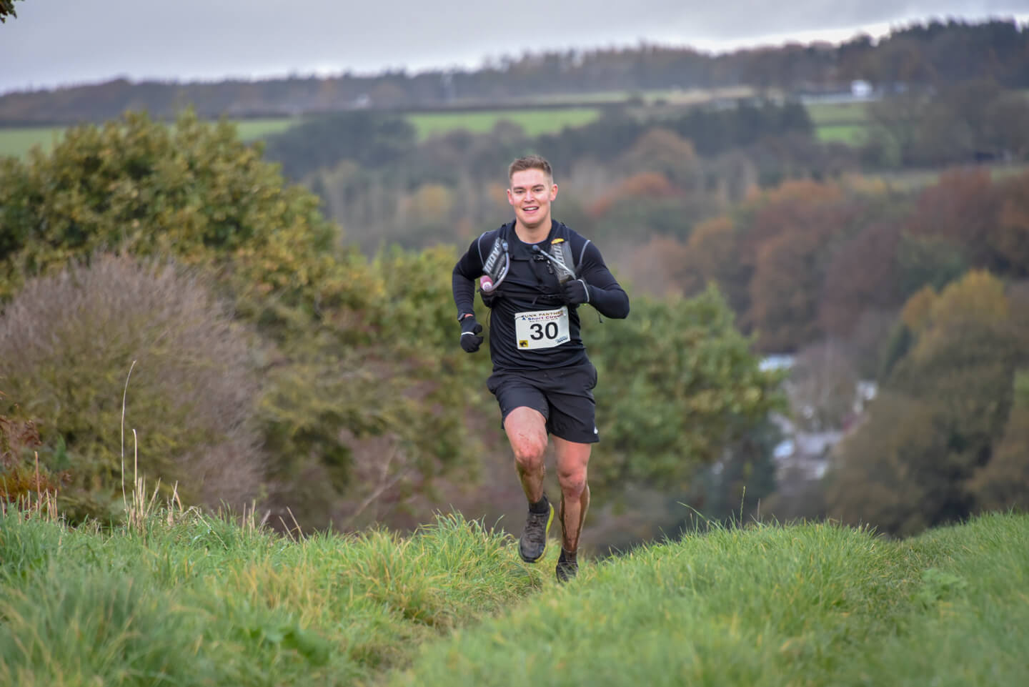 Young man running up to the brow of a hill during an ultramarathon race.
