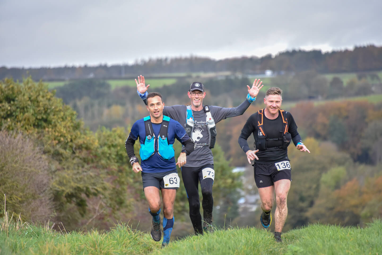 3 men running together during an ultramarathon through countryside.