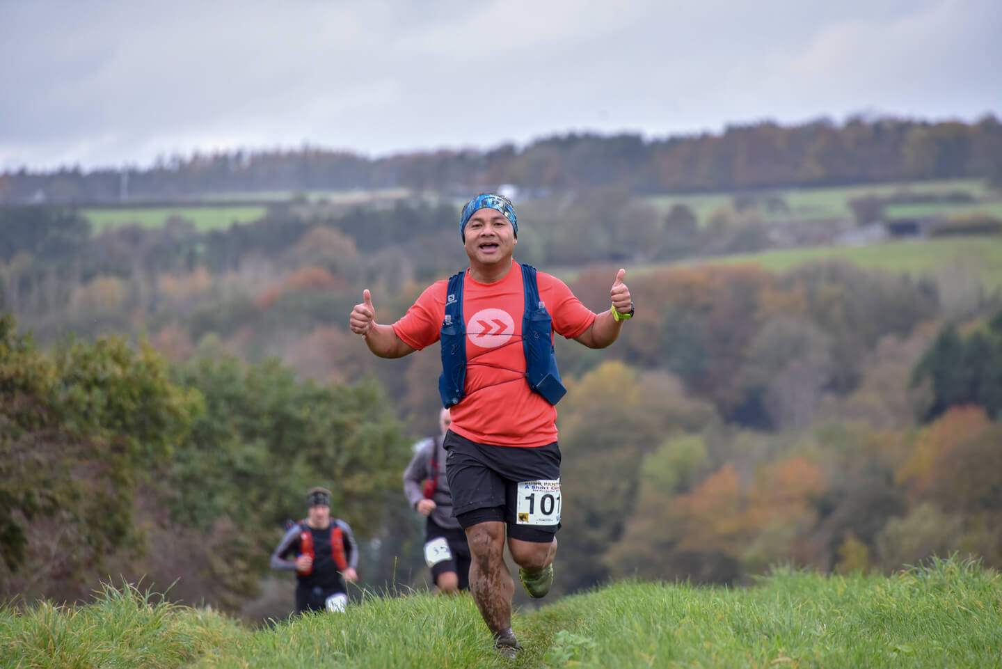 Man giving two thumbs up whilst running uphill in an ultramarathon