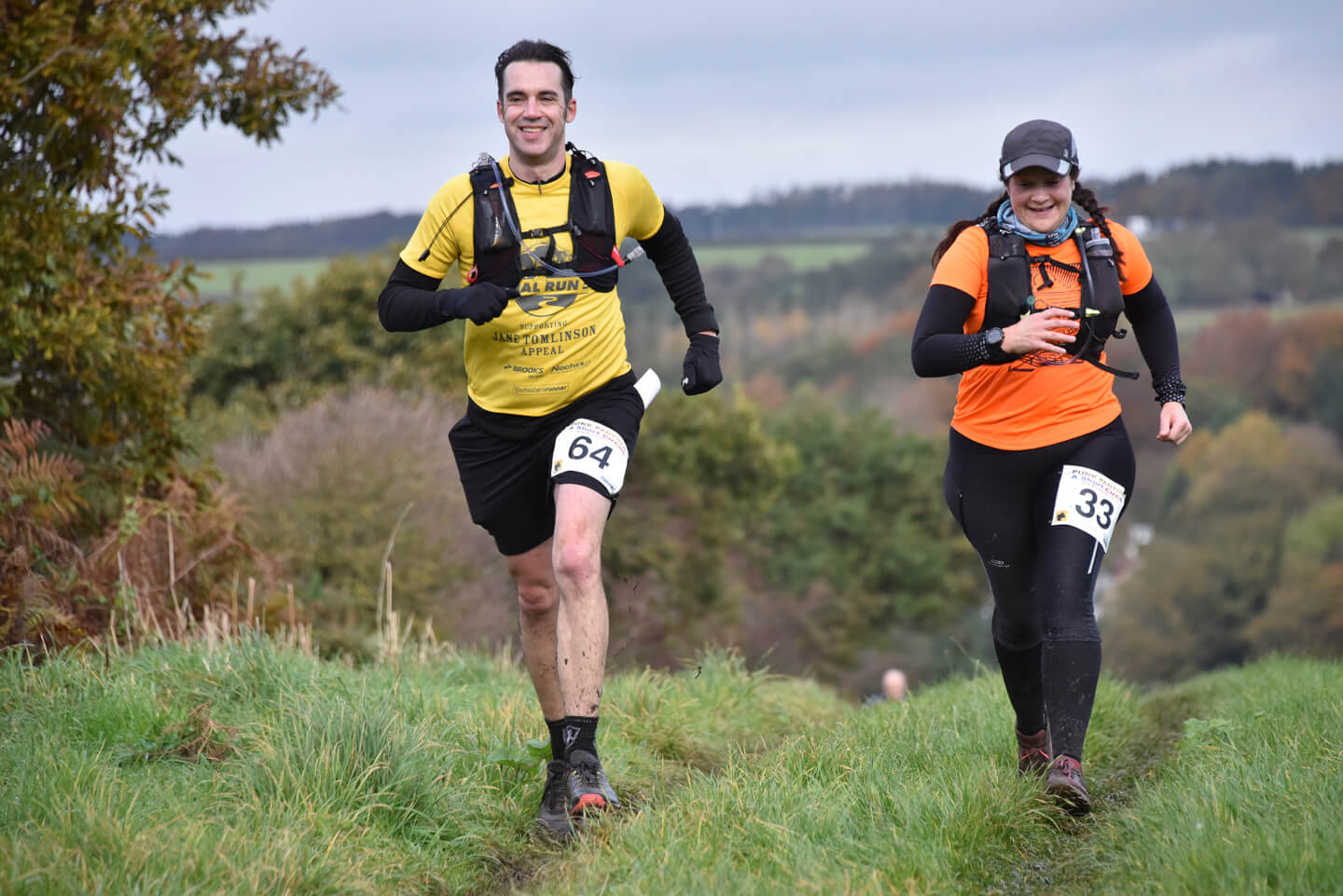 Man and woman running together during an ultramarathon in hilly woodland.