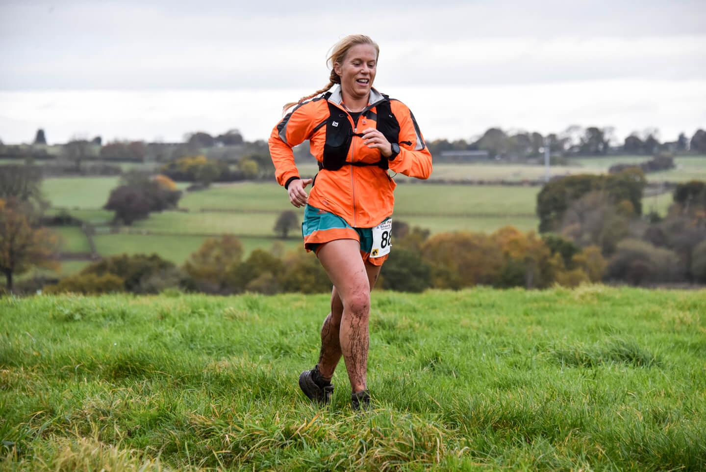 Woman running in orange jacket in ultramarathon race across countryside.