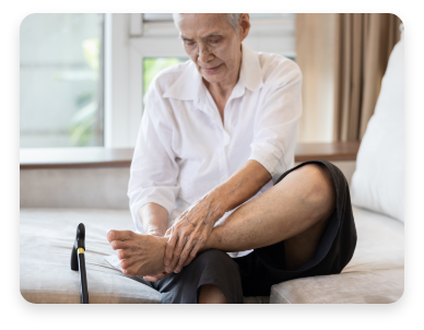 Older adult holding leg, likely claudication, a symptom associated with Peripheral Arterial Disease (PAD).