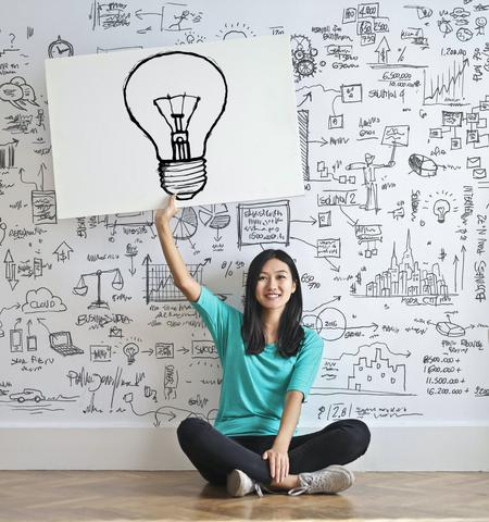 Woman holding up a card with a lightbulb on it signifying an idea