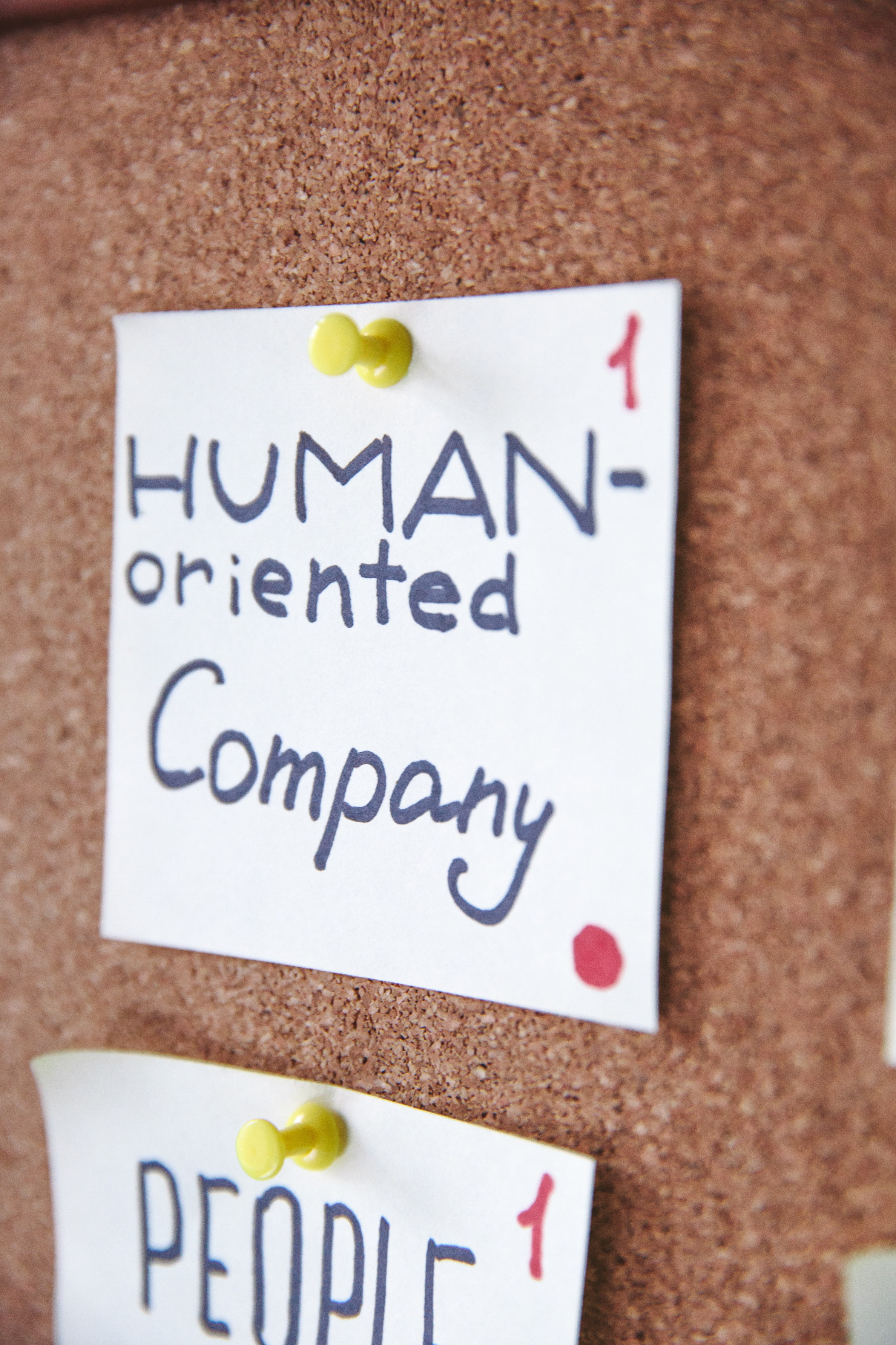 A sticky note on a pin board with 'Human-Orientated Company' written on it.