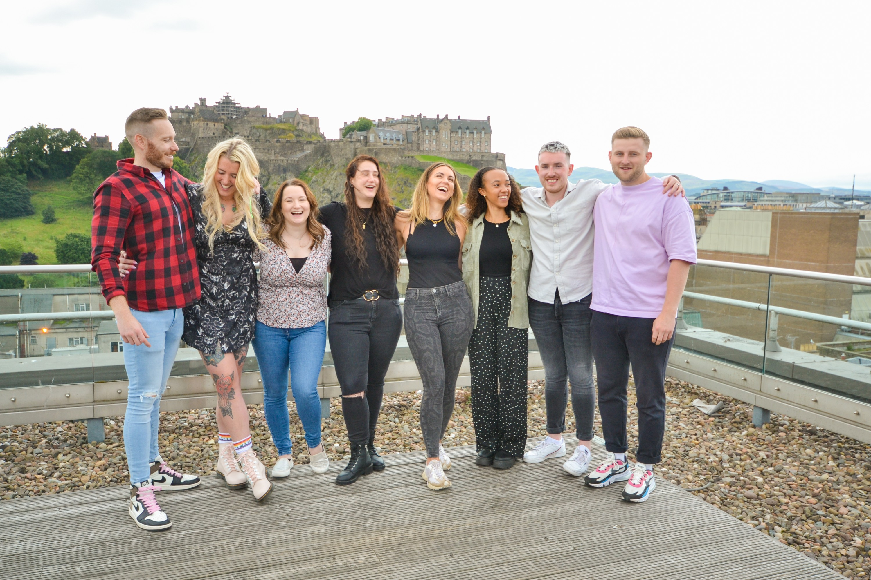 HappyCo. team members pictured smiling with Edinburgh castle in the background.