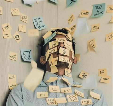 Burnt-out man with sticky notes over face
