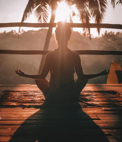 Women in yoga pose and sunset