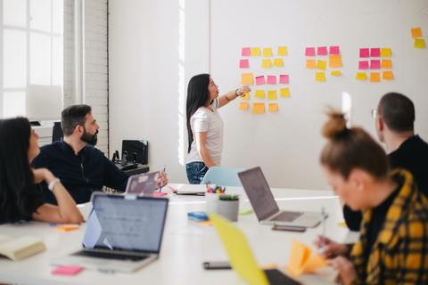 Woman giving presentation with sticky notes