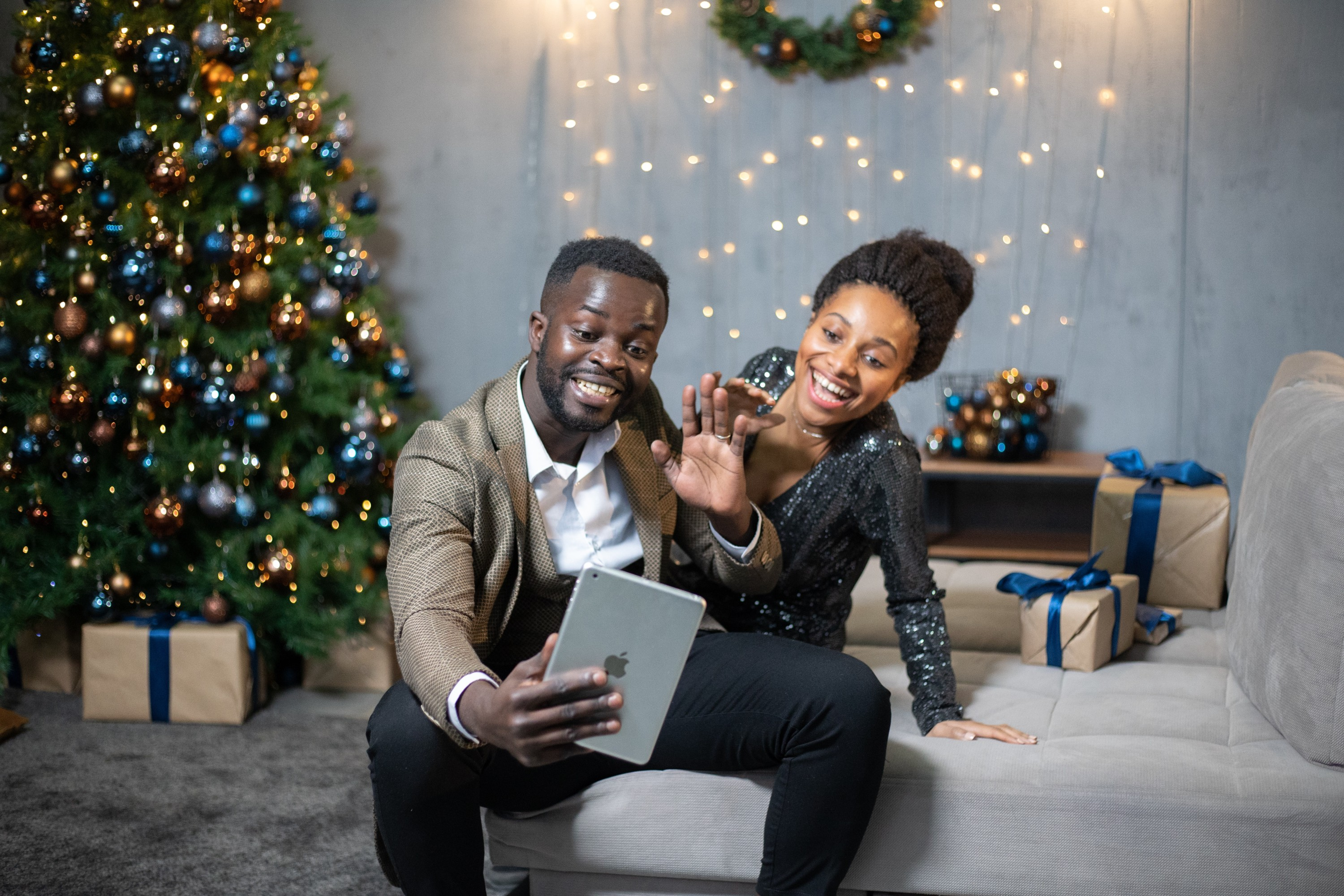 Two people infront of a Christmas Tree smiling at a handheld iPad