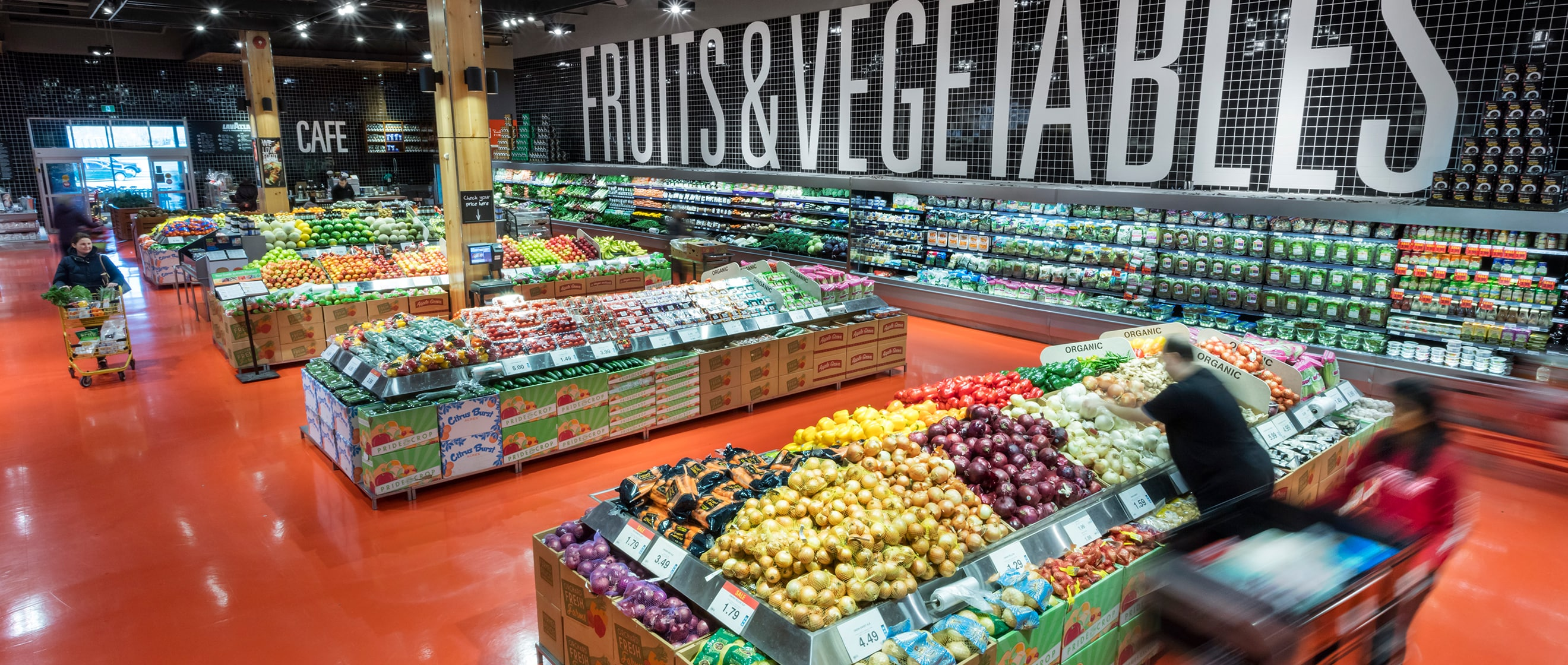 Fruits and vegetables section of a grocery store with fresh produce and people shopping.