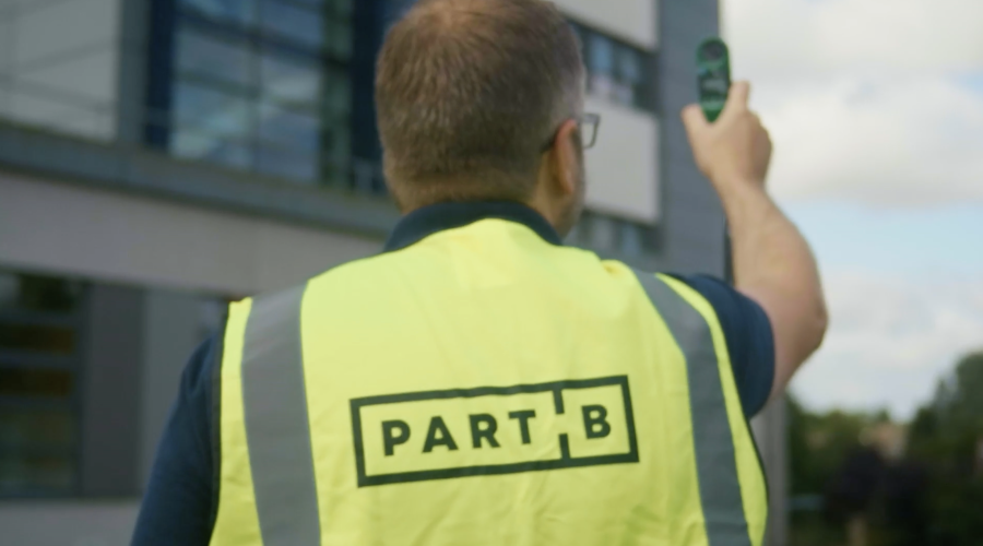 Jamie, PartB founder, conducting a survey - back to camera with hi-vis jacket on.