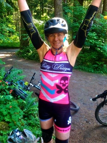 woman with arms raised after cycling