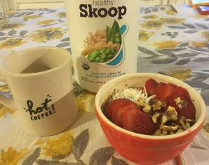 mug, bolw of oats with strawberries, healhty skoop container on table