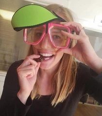 woman holding wearing snorkleing googles and eating chocolate