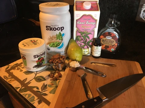 smoothie bowl ingredients on a table with cutting board, measuring spoons, and knife