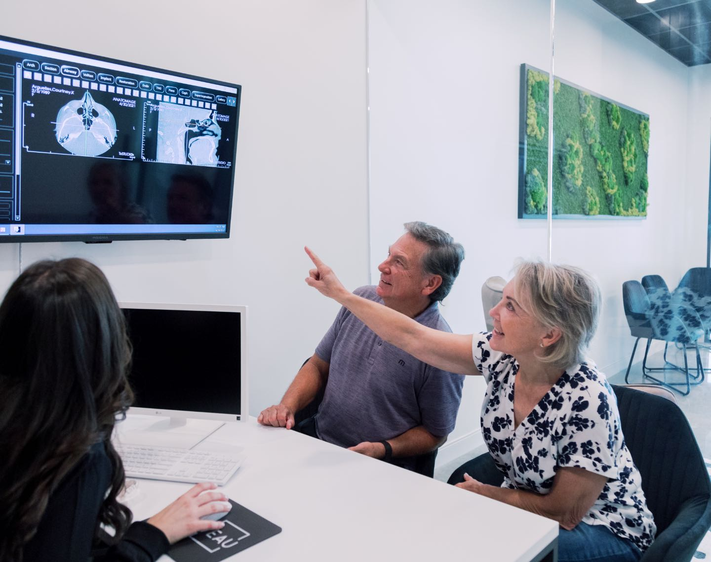 Photo of patients looking at a dental x-ray image on a screen