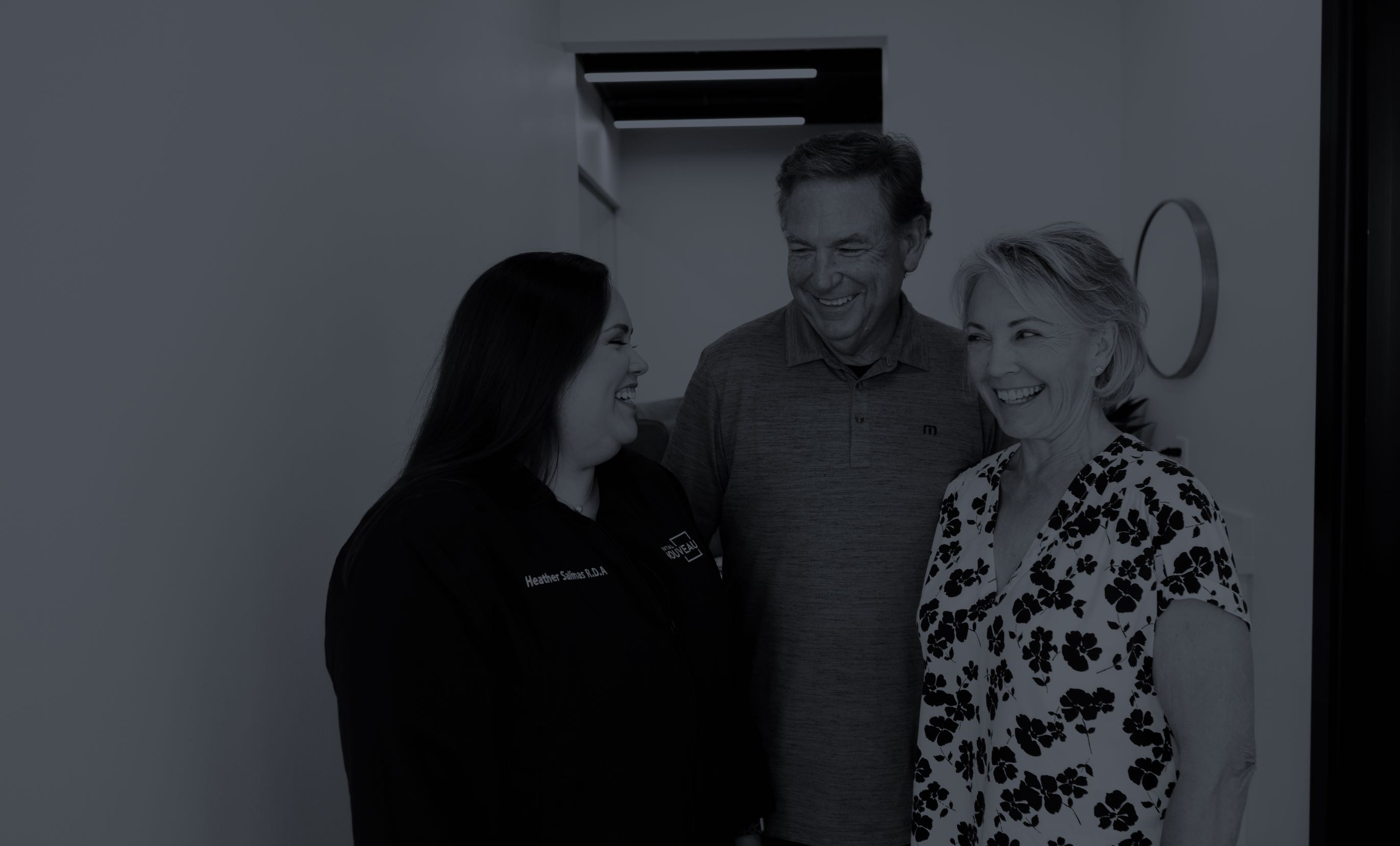 Photo of a team member and two happy dental patients