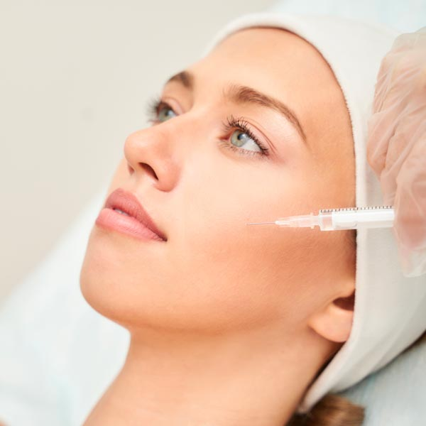 Injection on a woman's face in the cheek area.