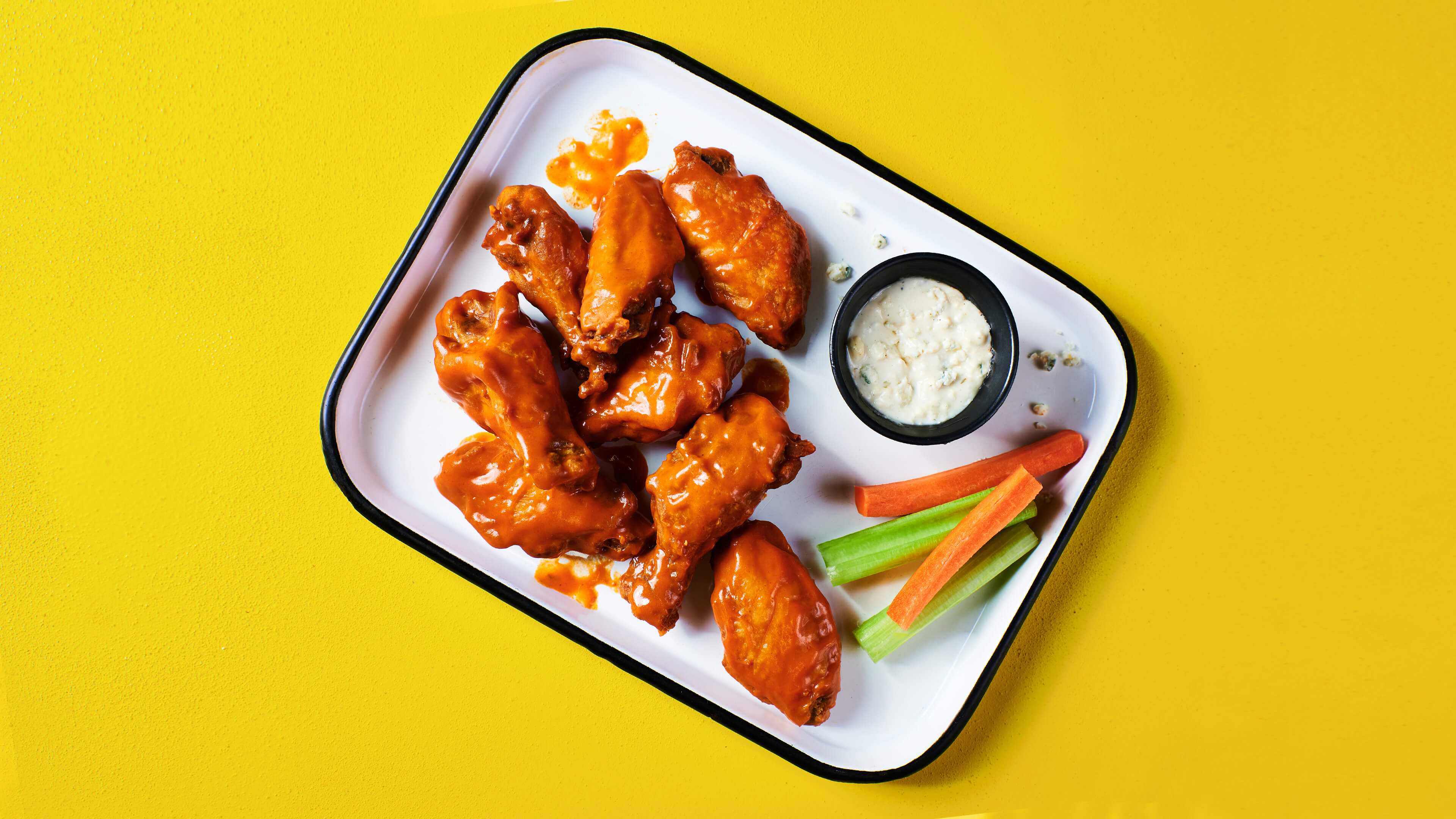 BIGGER BETTER BUFFALO WINGS - Big, juicy, meaty, tender and saucy buffalo wings, served with your choice of ranch or blue cheese, and crunchy celery and carrots for dipping.