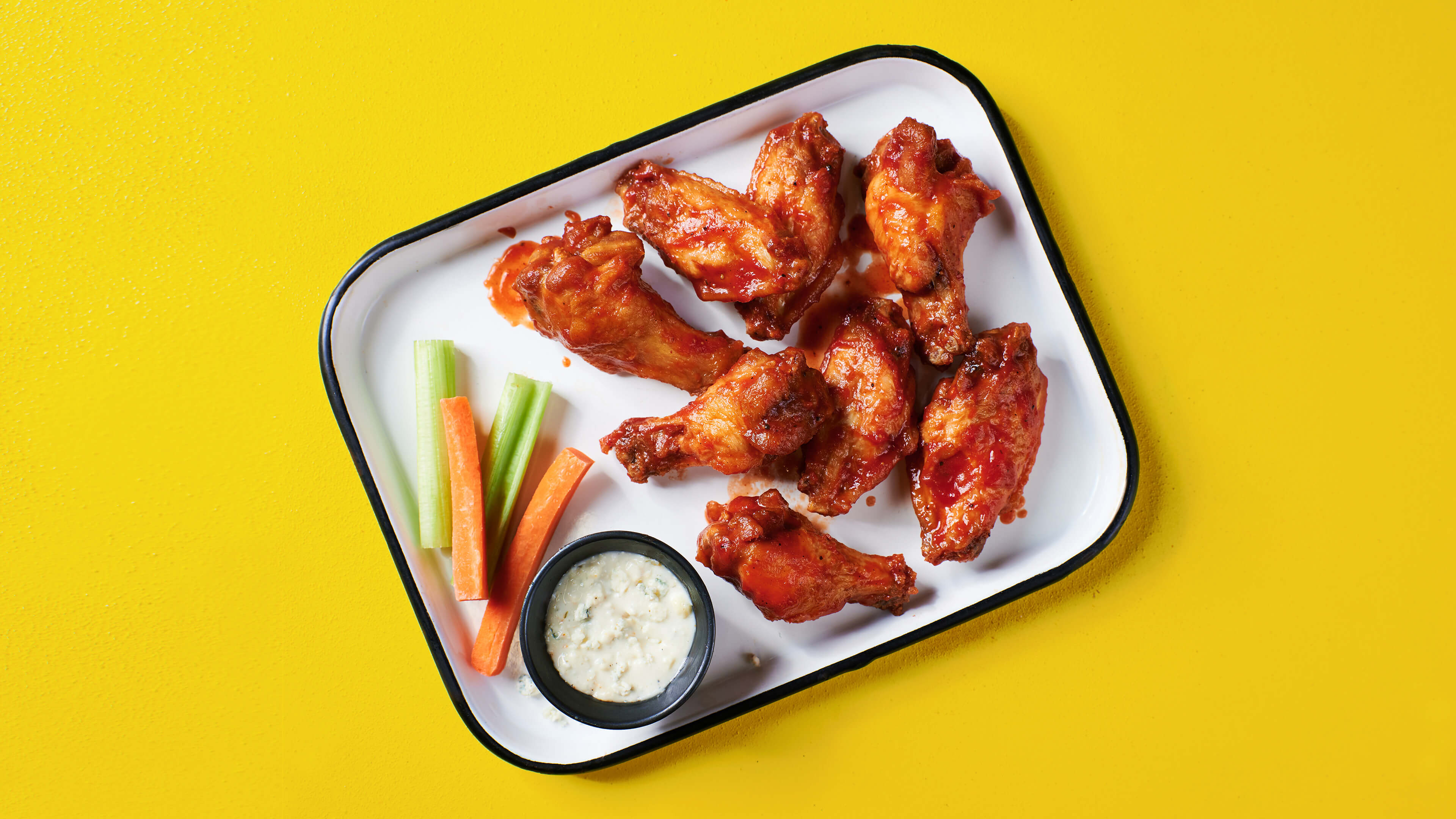 BIGGER BLAZIER BUFFALO WINGS - Big, spicy, juicy, meaty, tender and saucy buffalo wings, served with your choice of ranch or blue cheese, and crunchy celery and carrots for dipping.