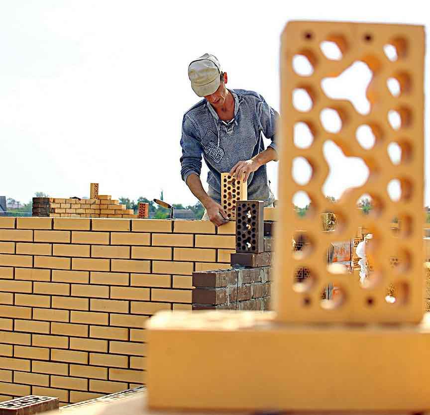 a mason laying bricks