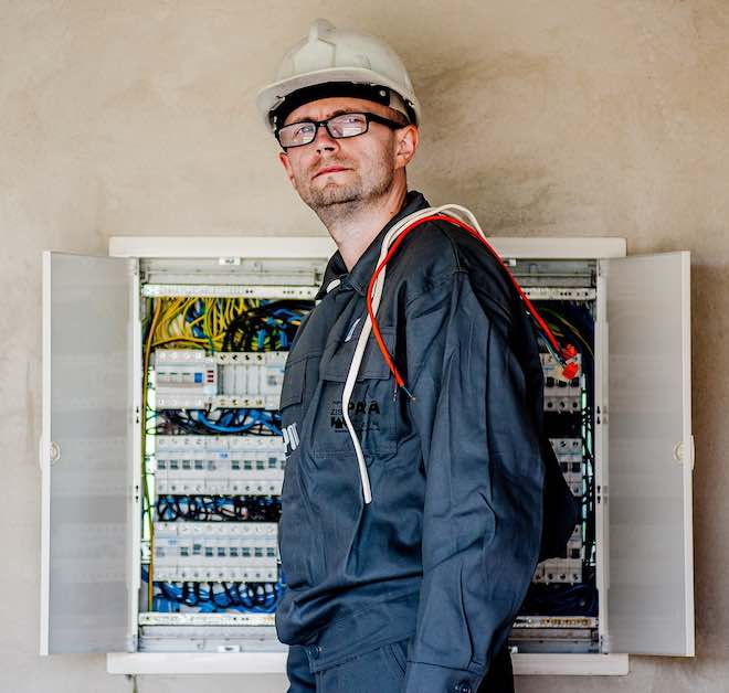 an electrician at a circuit breaker box