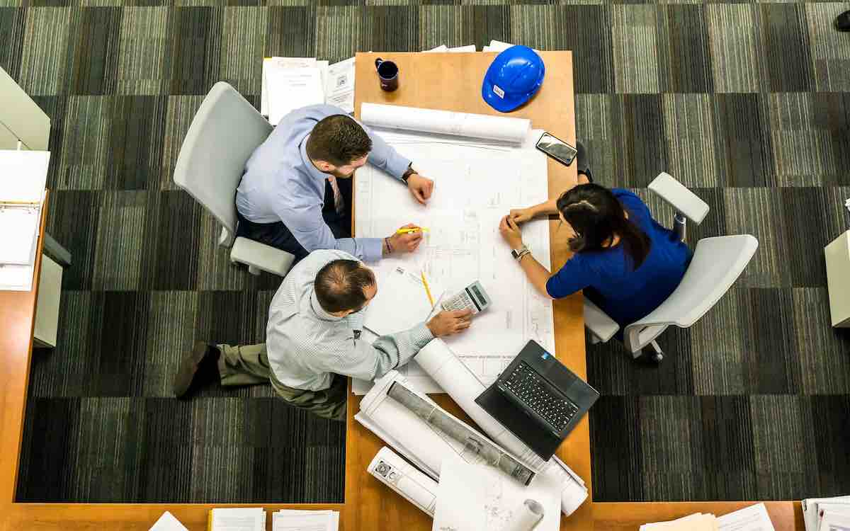 a construction meeting to review blueprints in an office