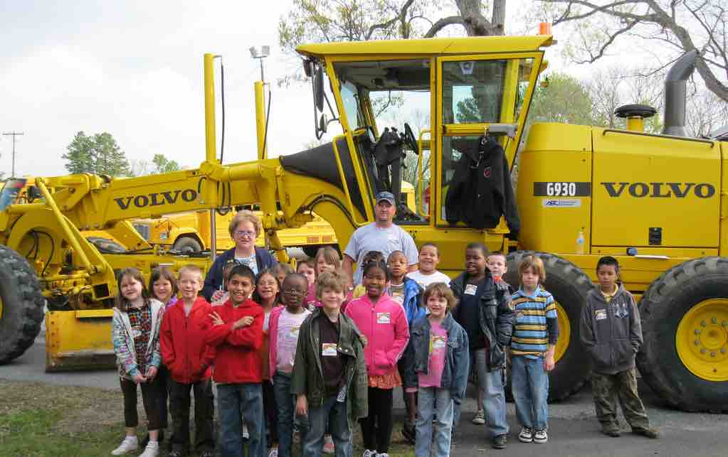 Schoolkids in front of heavy construction equipment