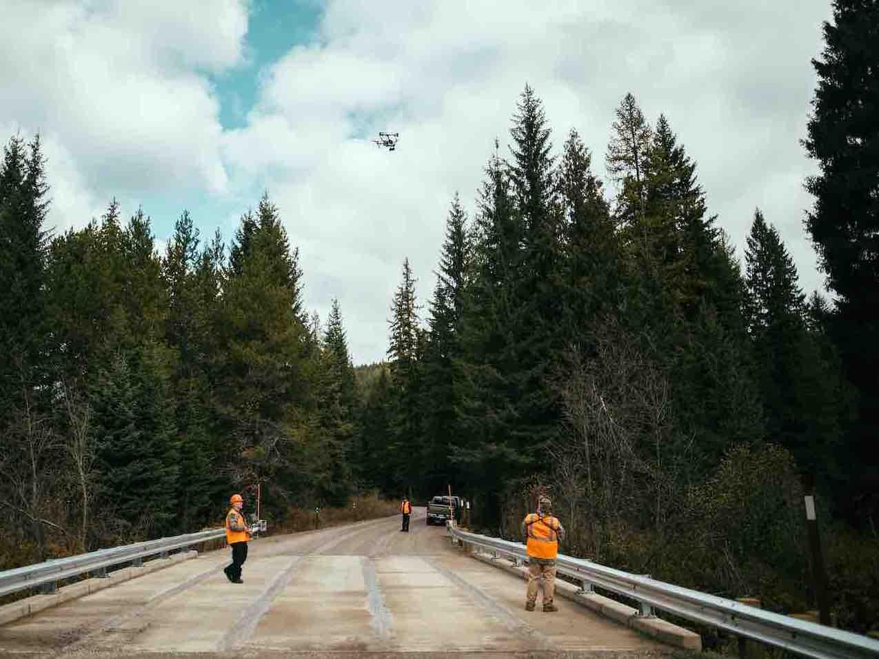 construction crew flying drone on bridge