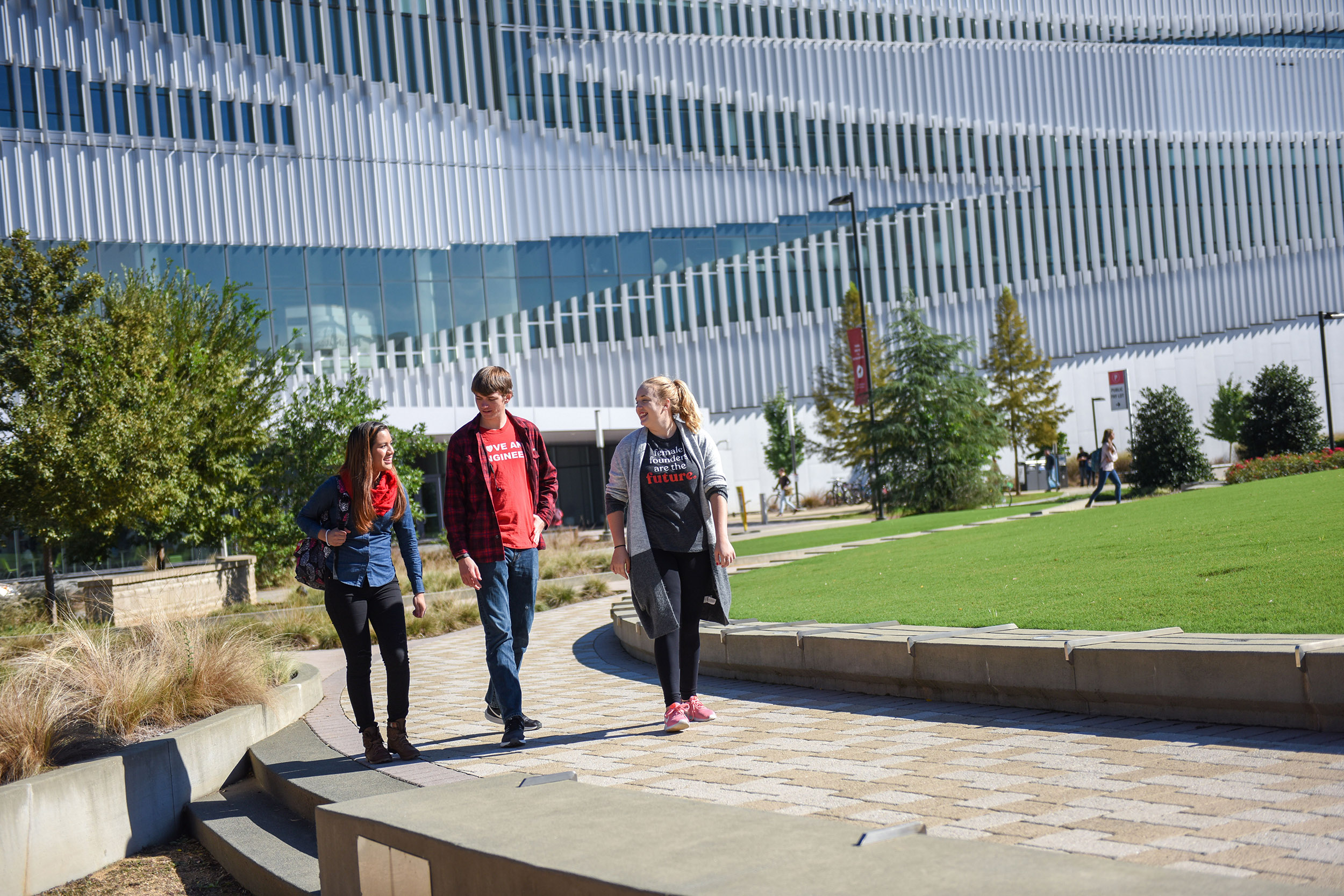 Students converse on a sunny day with the undulating forms of the Hunt Library behind them.