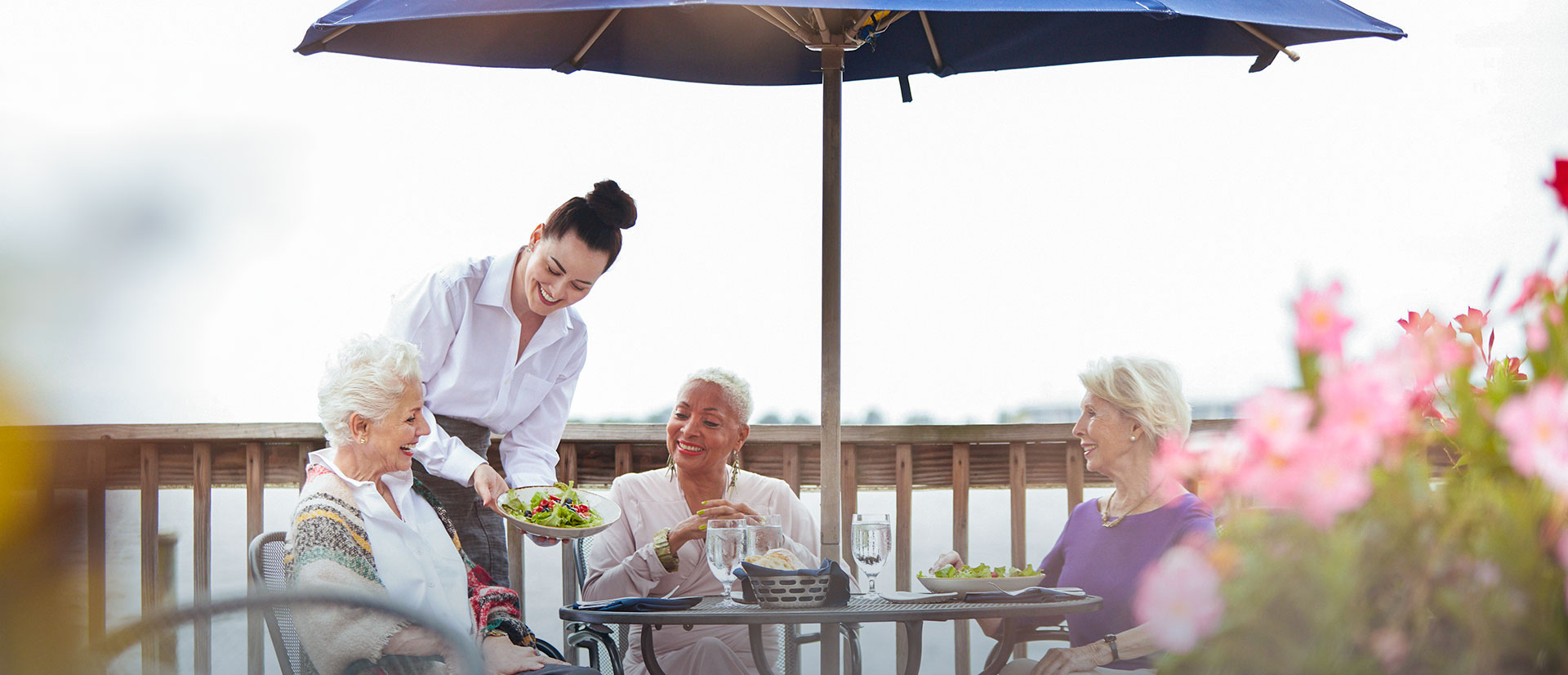 friendly seniors dining together on the water