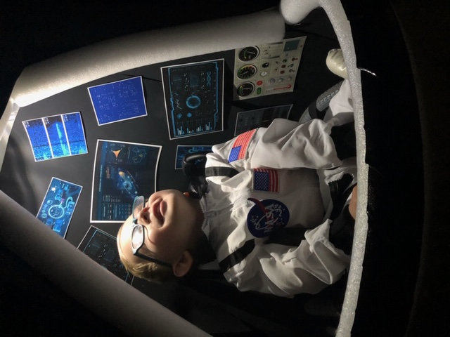 child with glasses in spacex capsule costume