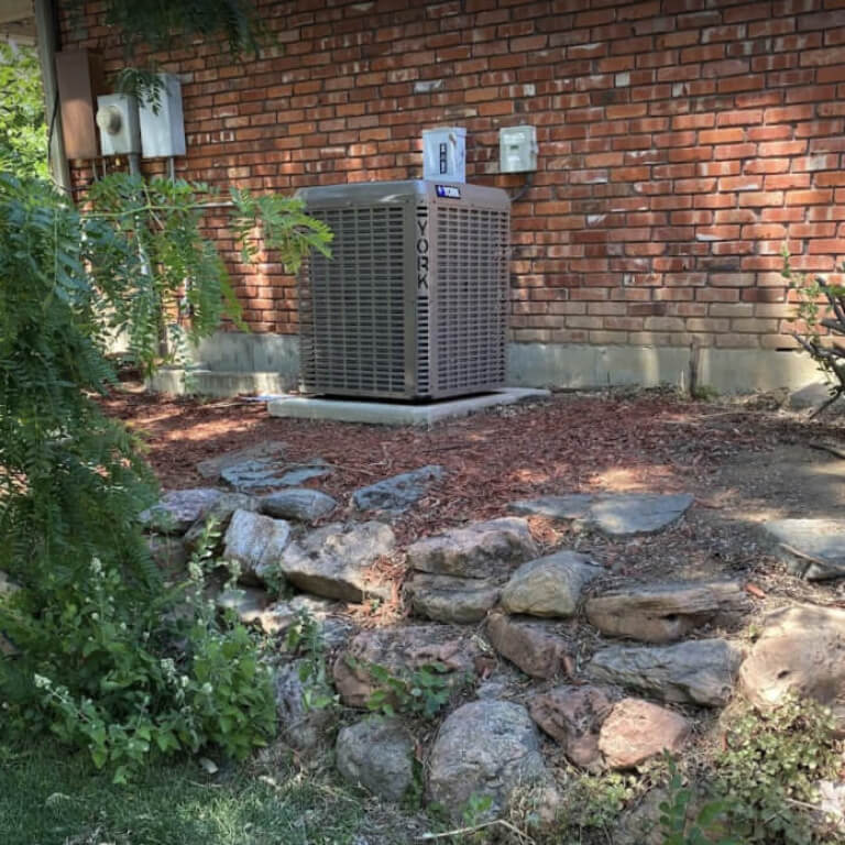 K&K Home solutions air conditioning unit outside of a residential brick building in the summer