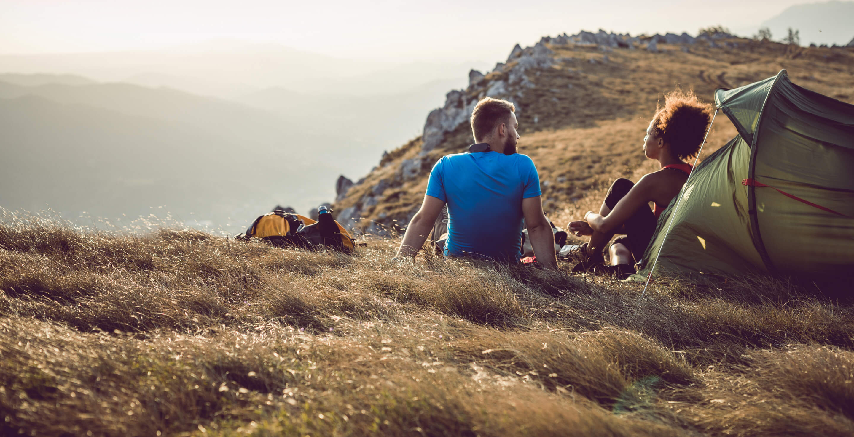 A couple camping atop a high dessert mountain