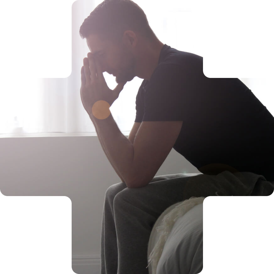 A man sitting up at the end of a bed, hands in front of his face, overcome with anxiety