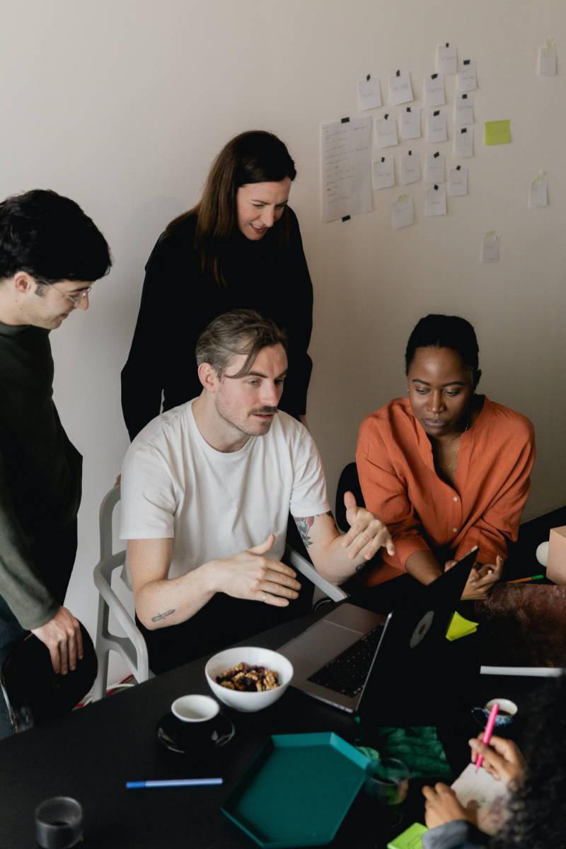 Office meeting where five team members discuss Webflow strategies.