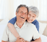 A happy elderly couple hugging and smiling.