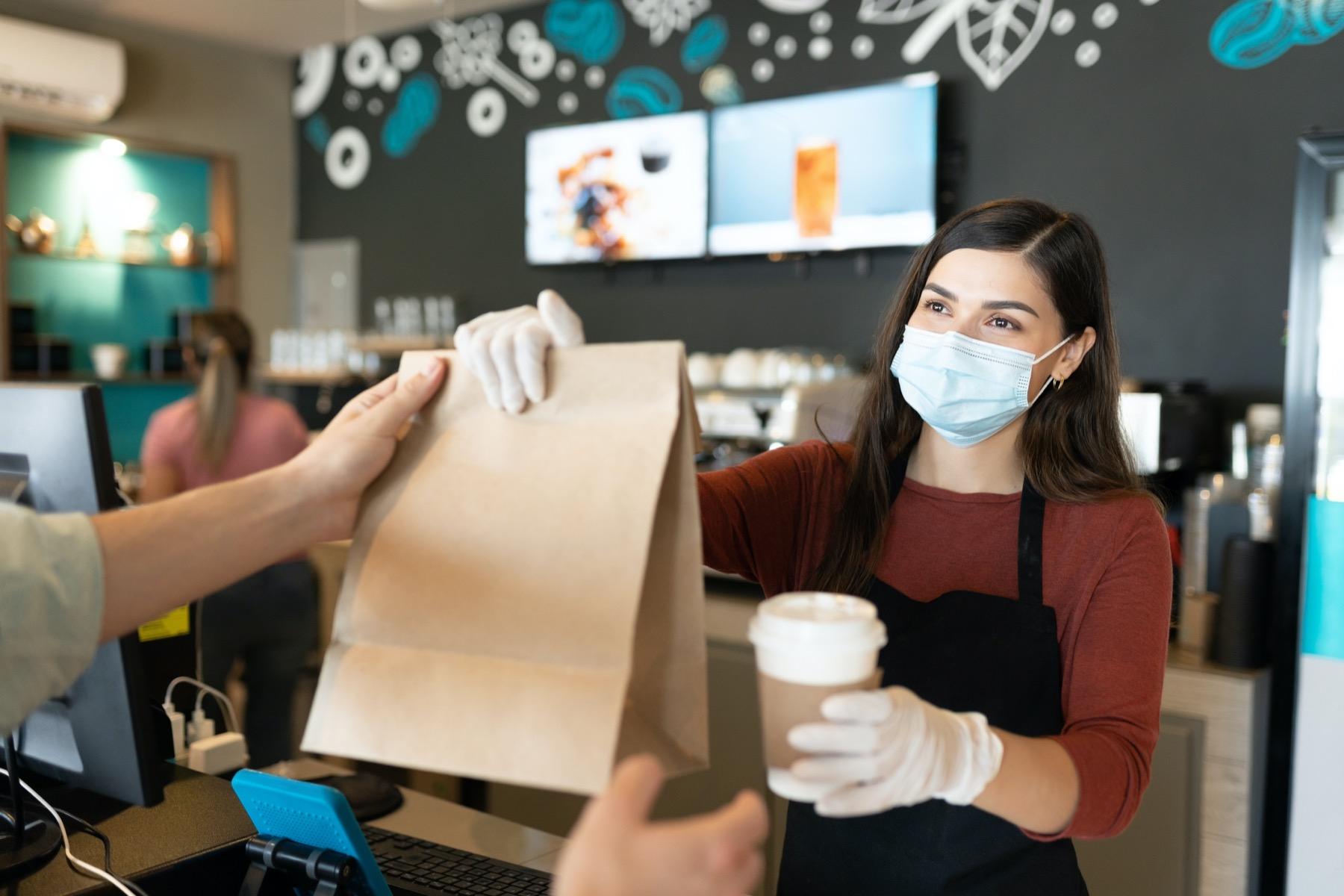 Restaurant worker handing food to customer