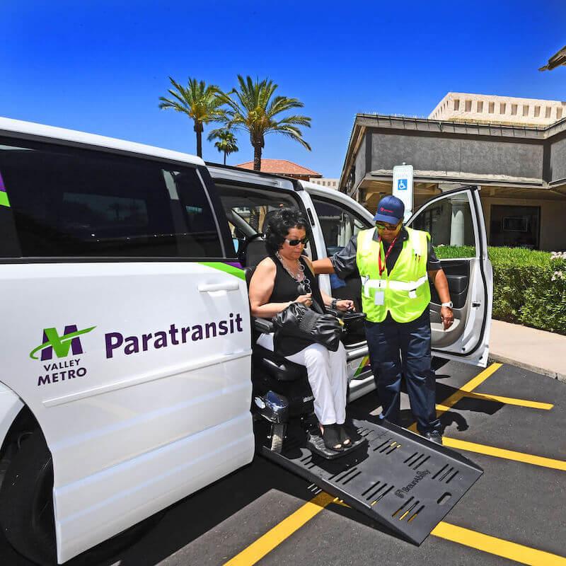 El conductor del paratránsito de Valley Metro ayuda al pasajero bajar del transporte público
