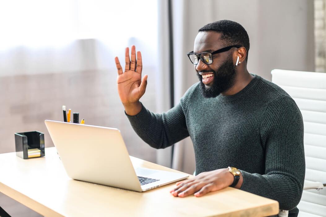 A web designer on laptop waving at computer