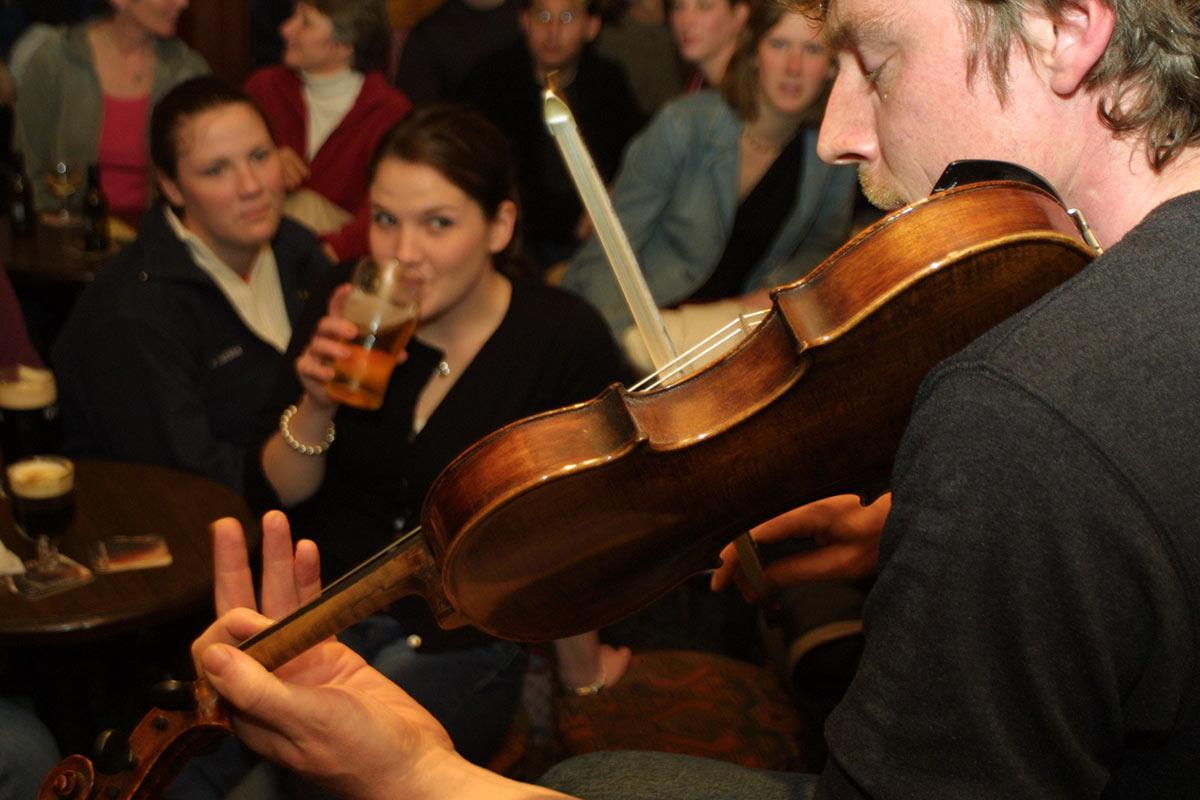 Man playing fiddle in Irish pub