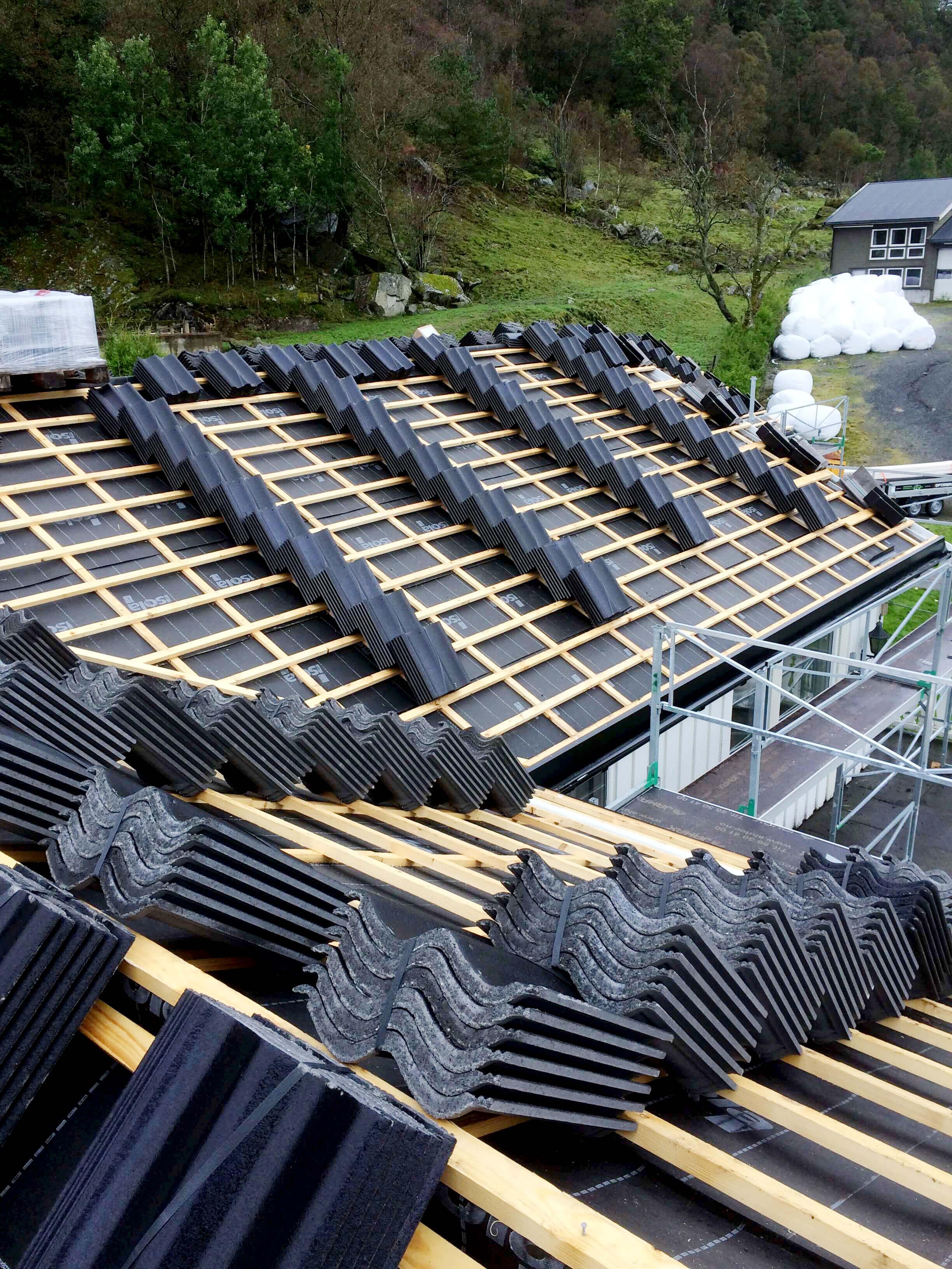 Rekker med takstein oppå tak ligger klare til å fordeles ut.