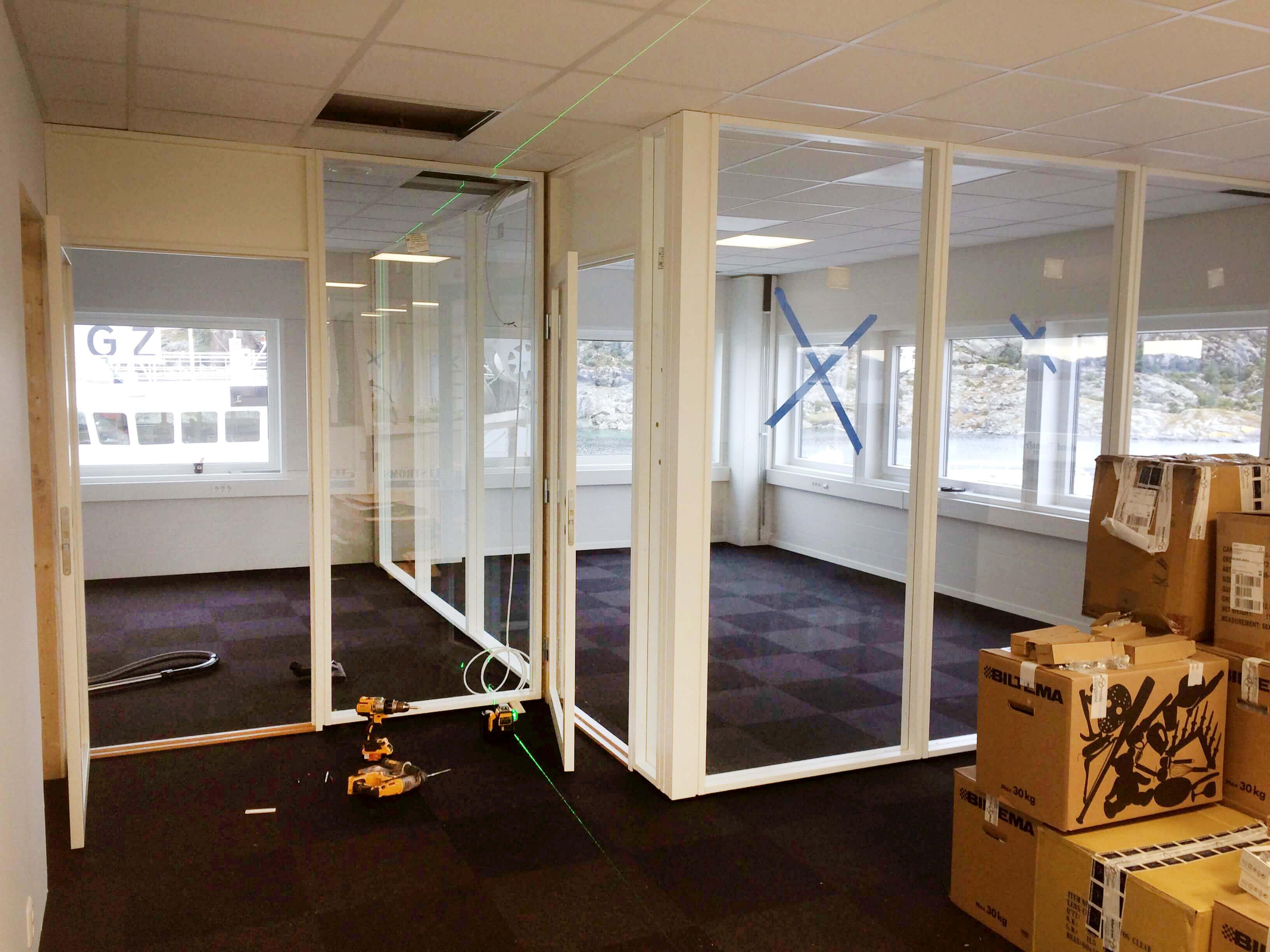 Innredning i kontorbygg med skillevegger av glass.