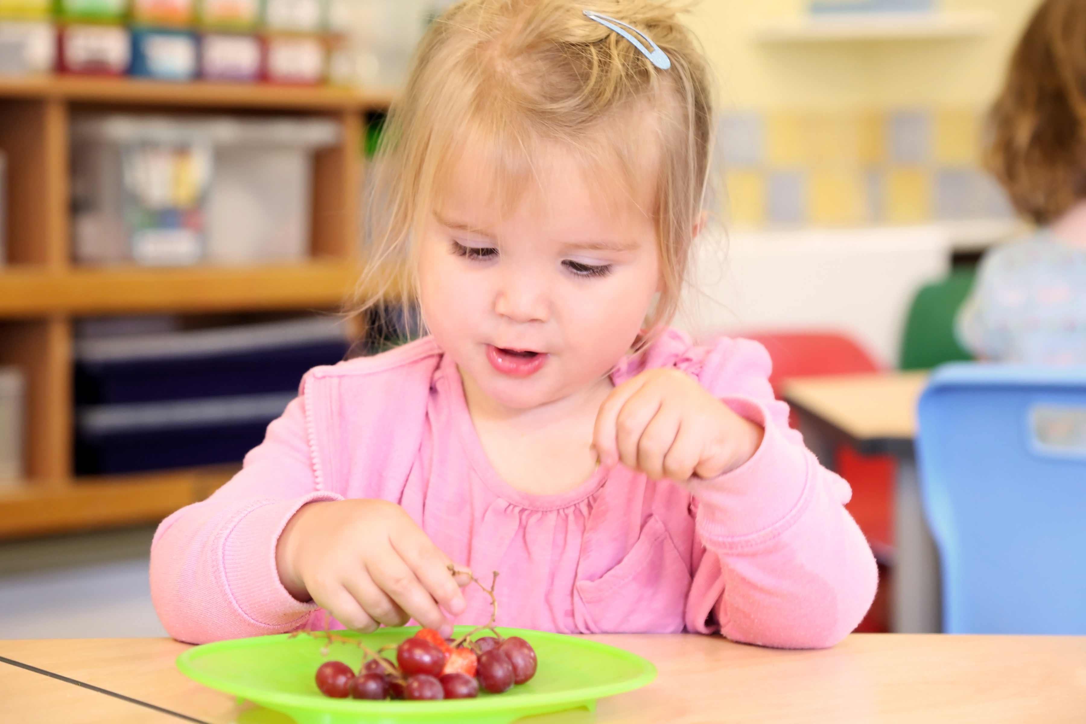Little girl eating grapes