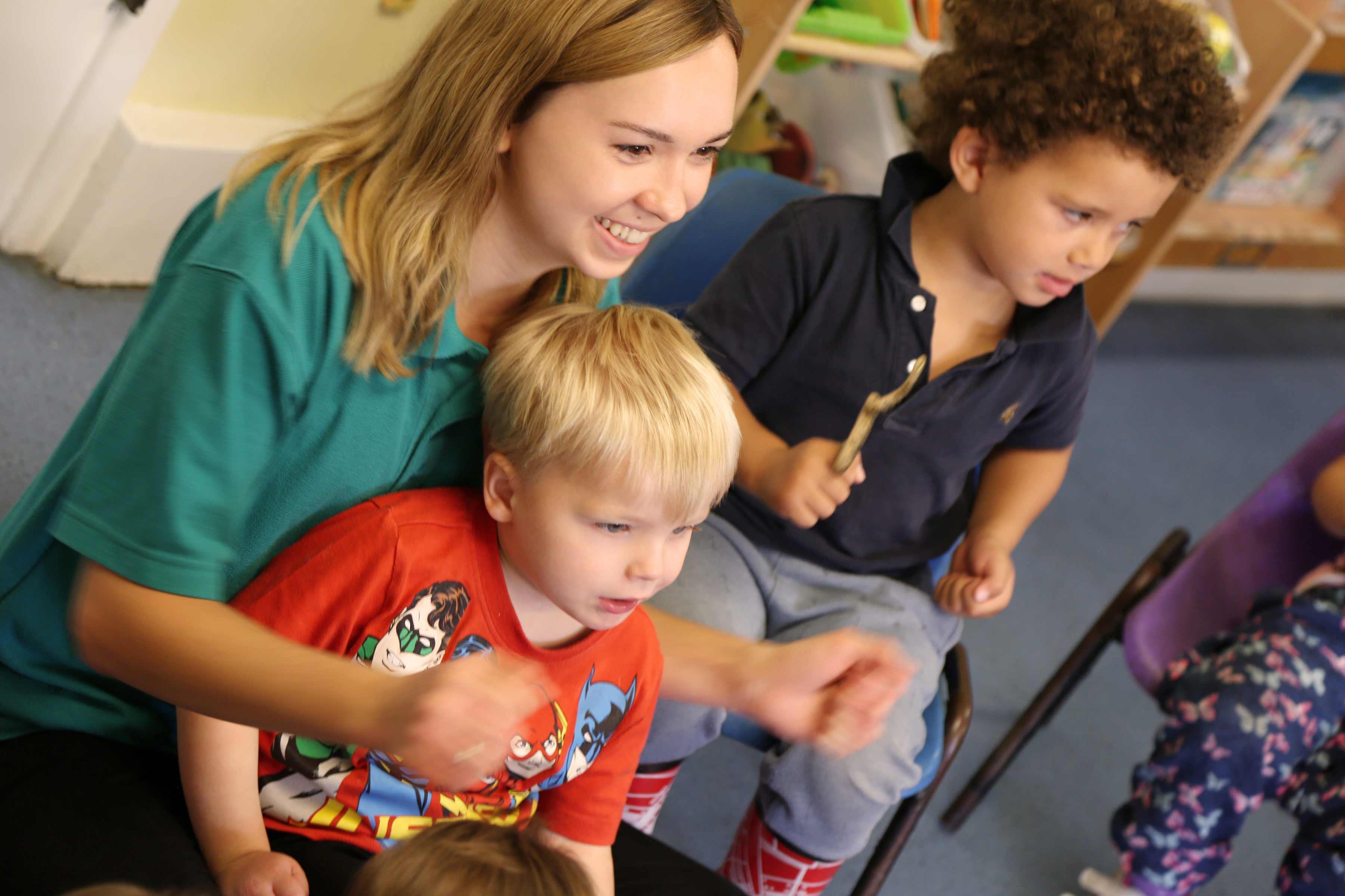 Teacher cuddling young boy playing a game