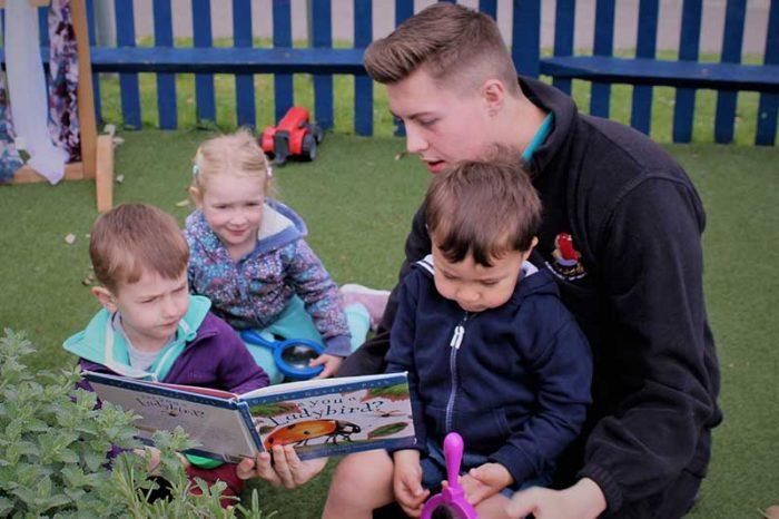 Teacher reading a book outside to children