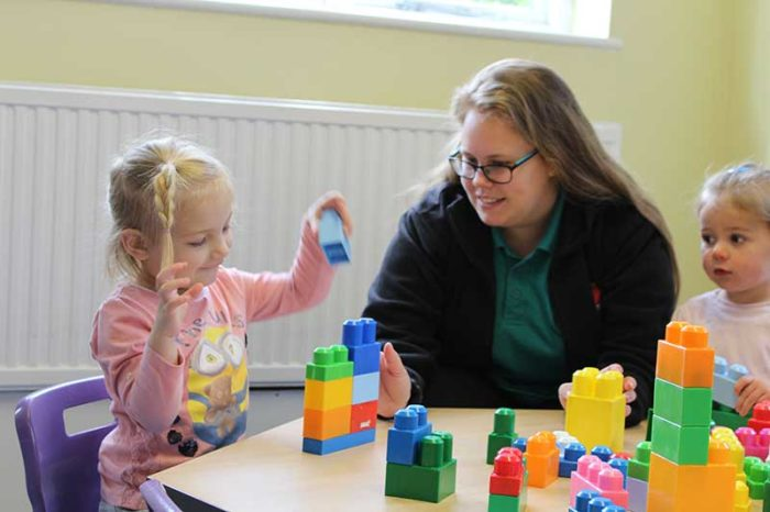 Young girl and teacher playing with building blocks
